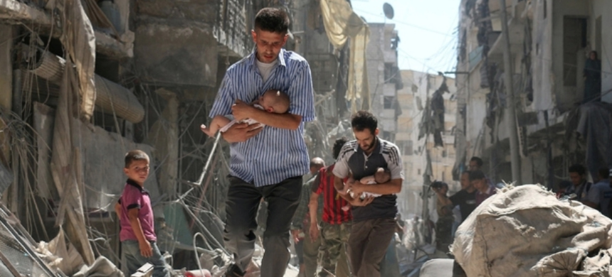 Syrian men carry babies through the rubble after an airstrike. (photo: Reuters)