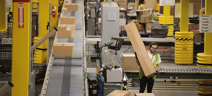 Workers pack and ship customer orders at an Amazon fulfillment center. (photo: Scott Olson/Getty Images)