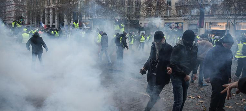 Protesters clash with riot police who fired tear gas canisters Saturday in central Paris. (photo: Getty Images)