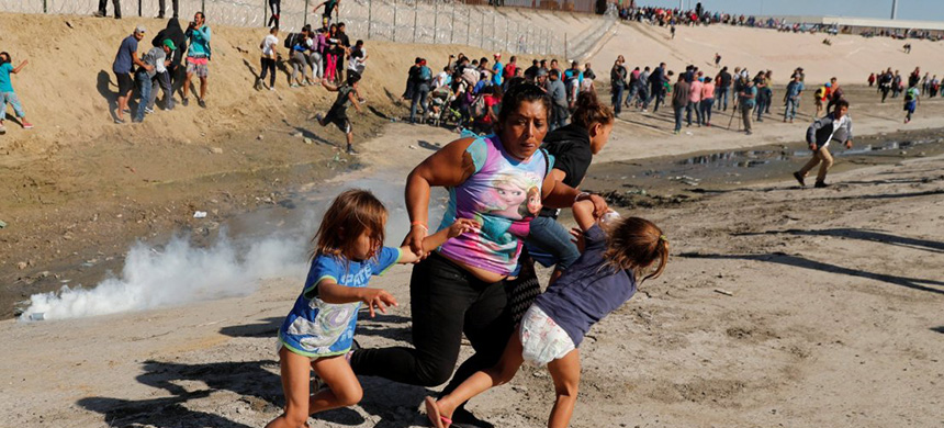 A migrant family, part of a caravan of thousands traveling from Central America en route to the United States, runs away from tear gas in front of the border wall between the U.S and Mexico in Tijuana, Mexico on November 25, 2018. (photo: Kim Kyung-Hoon/Reuters)