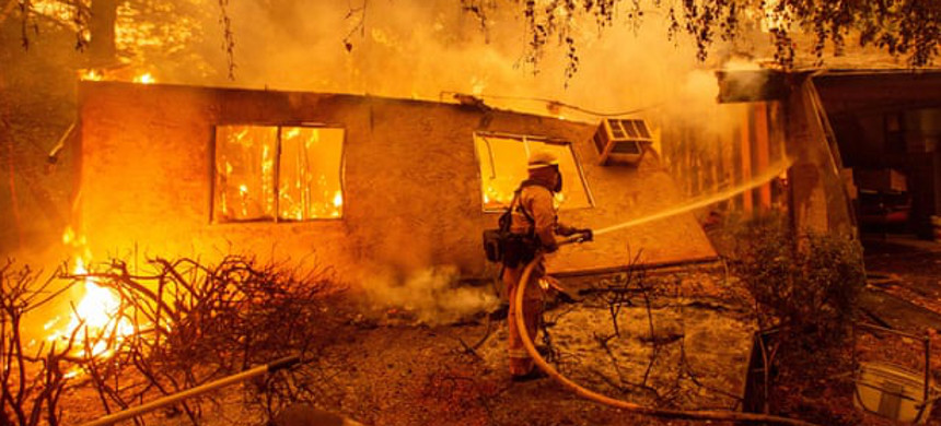 Firefighters battle flames at a burning apartment complex in Paradise, California, on 9 November. (photo: Josh Edelson/Getty)