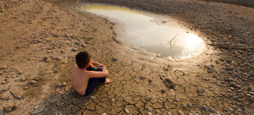 A boy sits in a dry farm field. (photo: National Drought Mitigation Center)