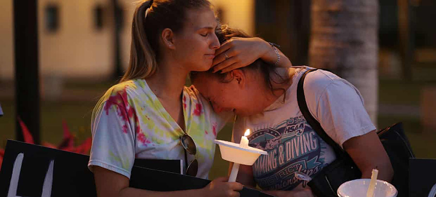 Two women attend a vigil in Boca Raton, Florida, on 16 February for the 17 people killed at a school shooting at Marjory Stoneman Douglas high school. (photo: Joe Raedle/Getty Images)