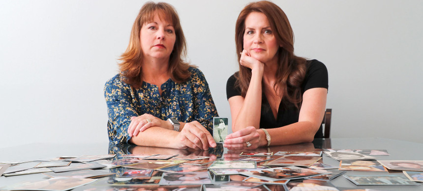 Cady Evans (left) and her sister, Crystal Deckard, surrounded by pictures of their mother, Darlene Coker, whose lawsuit against Johnson & Johnson 20 years ago was one of the first to allege that the company's Baby Powder caused cancer. (photo: Mike Blake/Reuters)