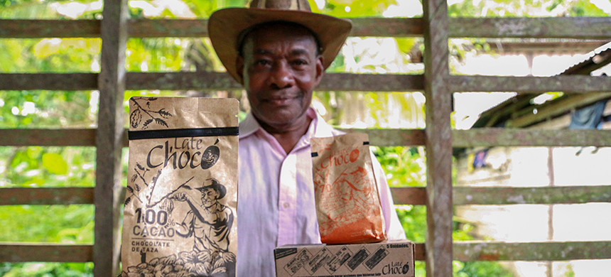 José Palacios, a cacao farmer, holds the Late Chocó chocolate products produced by his son, Joel, in Bogotá. The package bears an illustration of his likeness. José Palacios lives in Colombia's western Chocó department, which is also a coca-growing region. (photo: Verónica Zaragovia/NPR)