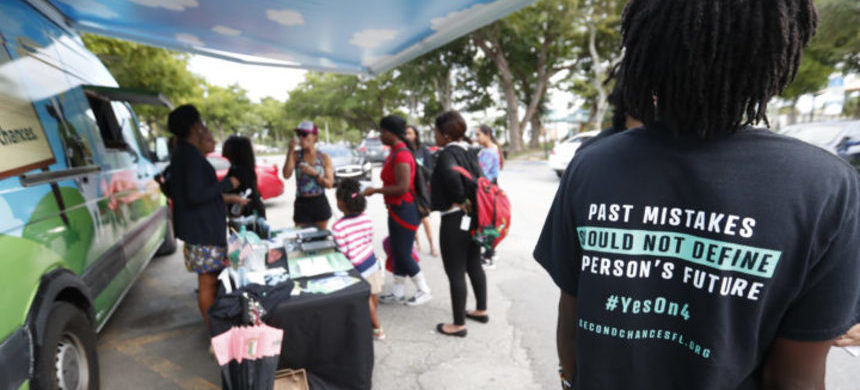 People gather around the Ben & Jerry's 'Yes on 4' truck as they learn about Amendment 4 at Charles Hadley Park in Miami, October 22, 2018. (photo: Wilfredo Lee/AP)