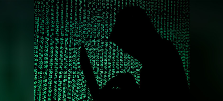 A hooded man holds a laptop computer as cyber code is projected on him in this illustration picture taken on May 13, 2017. (image: Kacper Pempel/Reuters)
