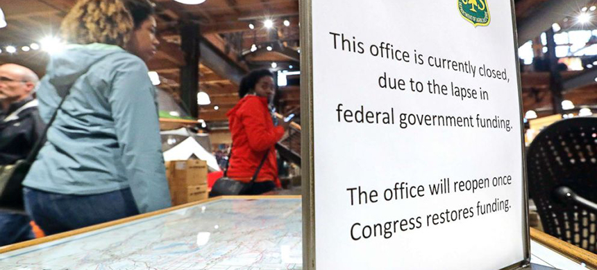 REI Co-op customers walk past an unstaffed ranger station kiosk, closed as part of the federal government shutdown, inside the flagship store in Seattle, December 26, 2018. (photo: AP)