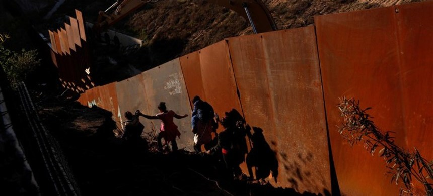 Migrants, part of a caravan of thousands from Central America trying to reach the United States, climb down a steep hill near the border wall into the U.S. from Tijuana, Mexico. (photo: Leah Millis/Reuters)