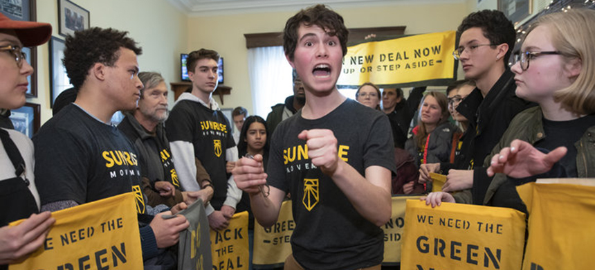 Jeremy Ornstein of Watertown, Massachusetts, cheers on fellow environmental activists as they occupy the office of Rep. Steny Hoyer (D-Md.) to press for Democratic support for a Green New Deal. (photo: J. Scott Applewhite/AP)