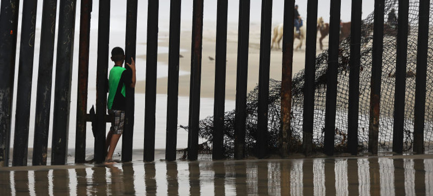 A child moves through the border wall. (photo: Mario Tama/Getty)