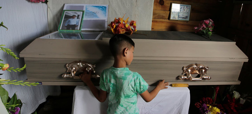 A child touches the coffin of Nelson Espinal, who was shot dead outside his home on 18 December 2018 in Tegucigalpa, Honduras. (photo: Jorge Cabrera/Reuters)