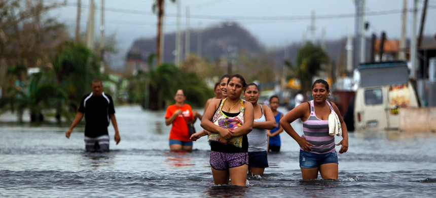 People wade through flooded streets following Hurricane Maria in Puerto Rico. (photo: Getty)