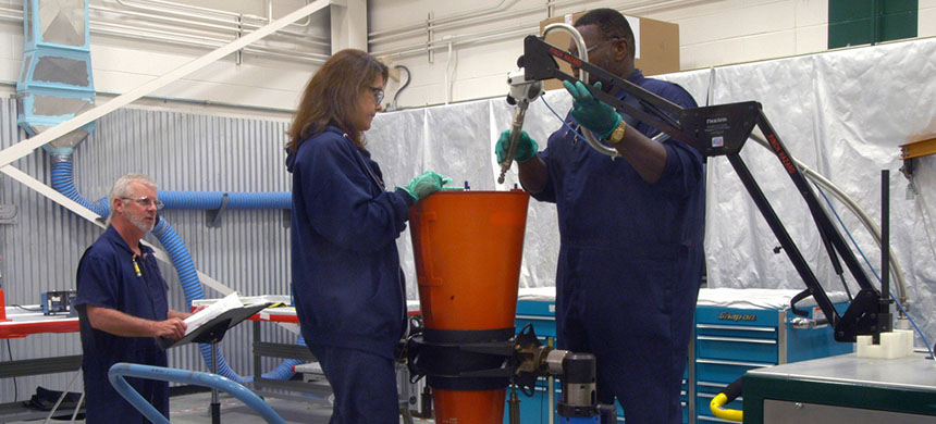 Two Pantex production technicians work on a W76 while a co-worker reads the procedure step-by-step. (photo: NNSANews)