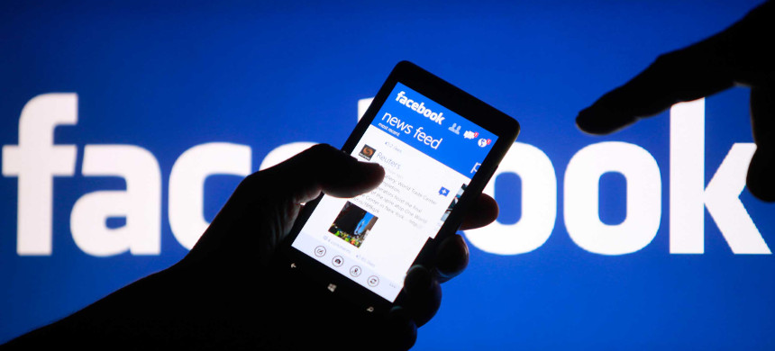 A smartphone user shows the Facebook application on his phone. (photo: Dado Ruvic/Reuters)