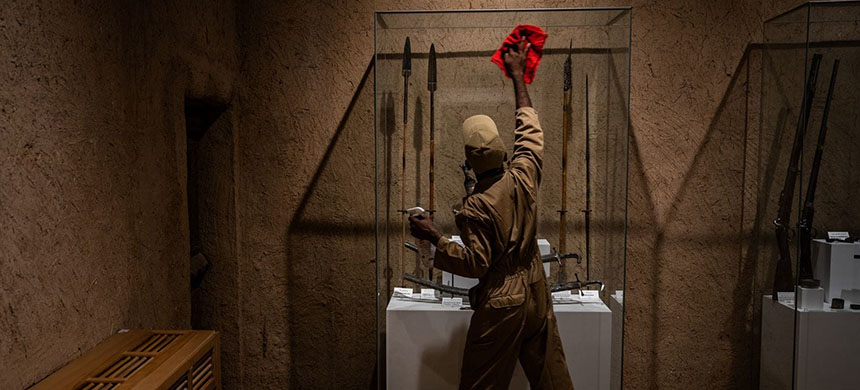 A worker cleans a museum display case in Riyadh. The departure of more than 1 million foreign workers since 2017 has added to a sense of uncertainty in Saudi Arabia. (photo: Salwan Georges/AP)