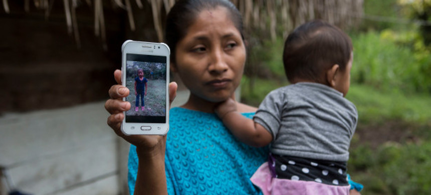 The mother of Jakelin Caal holds up a picture of her on her cell phone. (photo: AP)