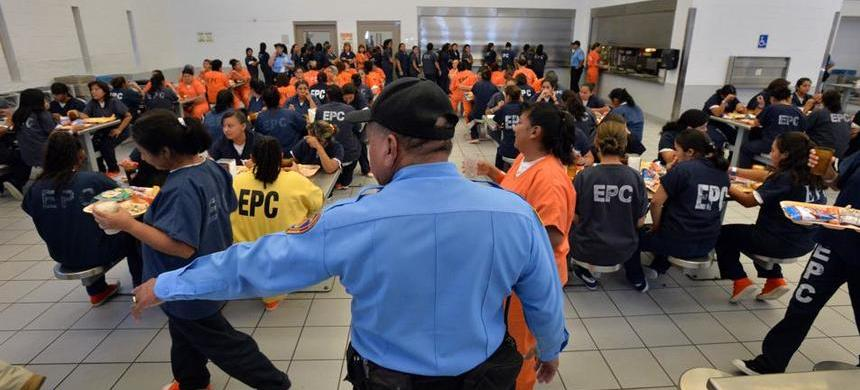 A U.S. Immigration and Customs Enforcement officer directs detainees during lunch time in cafeteria at the El Paso Processing Center in El Paso, Texas. (photo: Hyosub Shin)