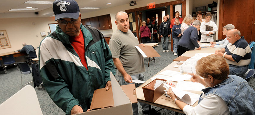 Commissioners in Sandusky, Ohio, have voted to make Election Day a city holiday, in place of Columbus Day. Sandusky resident Moses Croom is seen here voting at a polling station at a local library in November 2008. (photo: Jason Werling/Sandusky Register)