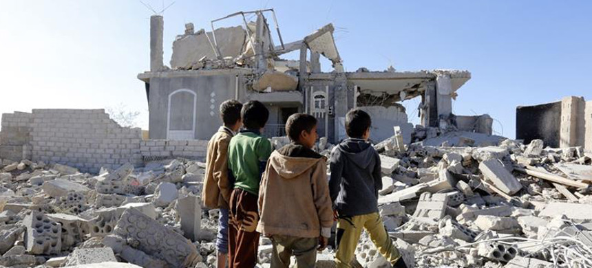 Children stand near a home destroyed in a Saudi coalition air strike. (photo: AFP)