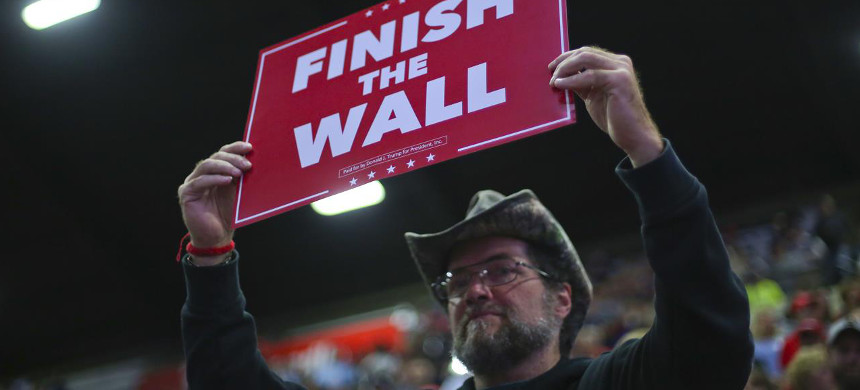 Donald Trump supporter holds sign calling for border wall to be built. (photo: Getty)