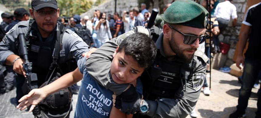 Israeli security forces hold a Palestinian child in a chokehold. (photo: AFP)