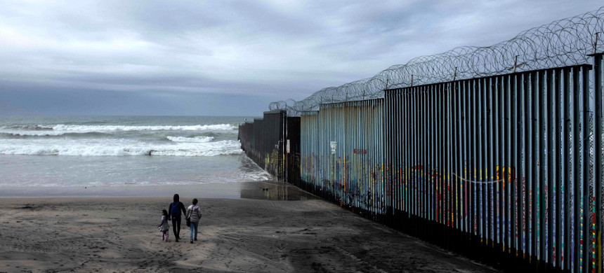 A family of migrants walk on the beach near the U.S.-Mexico border fence at Playas de Tijuana, Mexico, on Jan. 16, 2019. (photo: Guillermo Arias/Getty)