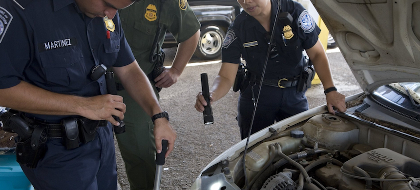 Border Patrol agents inspect a vehicle. (photo: Gilles Mingasson/Getty Images)