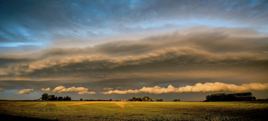 Clouds over a farm field. (photo: Philippe Huguen/Getty)