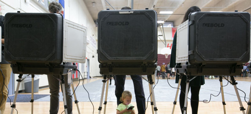 Sloane (no last name given), 2, waits between her father's legs as he and other voters cast their ballots at a polling station set up at Grady High School for the mid-term elections on November 6, 2018, in Atlanta, Georgia. Georgia has a tight race to elect the state's next governor. (photo: Jessica McGowan/Getty)
