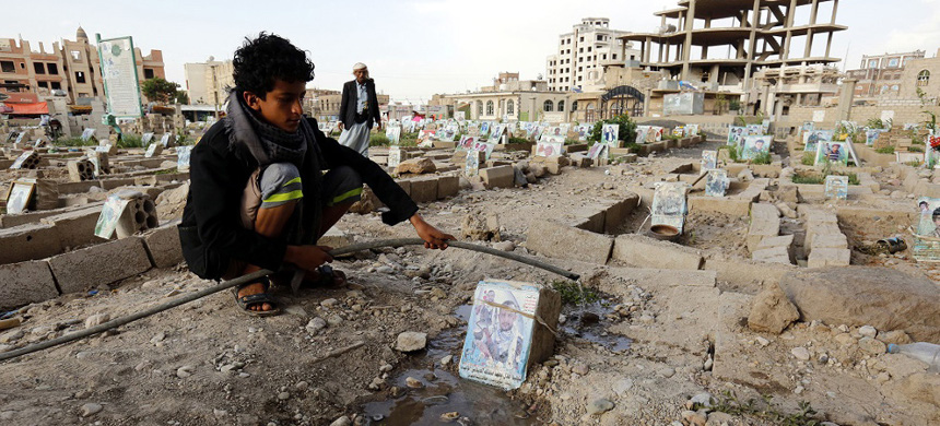Young man at a grave in Yemen. (photo: EPA)