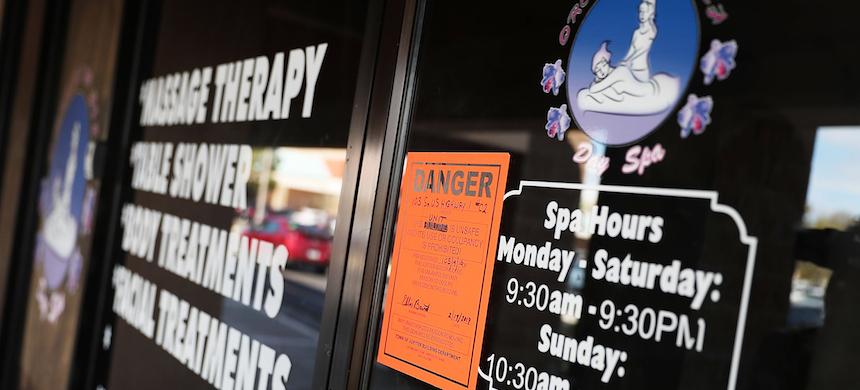 A danger sign is seen on the front door of the Orchids of Asia Day Spa in Jupiter, Florida, February 22, 2019. (photo: Joe Raedle/Getty Images)