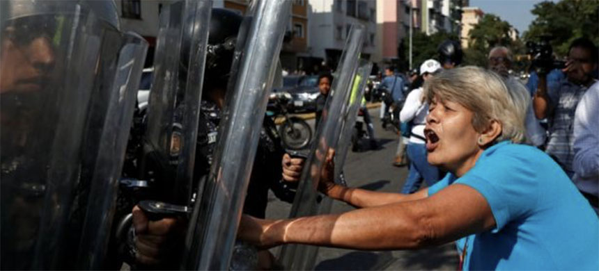 Opposition protesters confronted police in Caracas ahead of the march. (photo: Reuters)