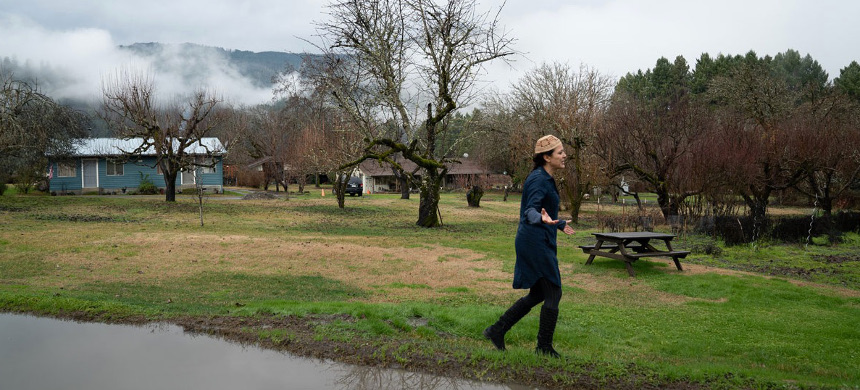 Lisa Hillman walks around her home, surrounded by forest, where the traditional fire-mitigation practice of controlled burning is illegal without special permit. (photo: Laurence Du Sault/High Country News)