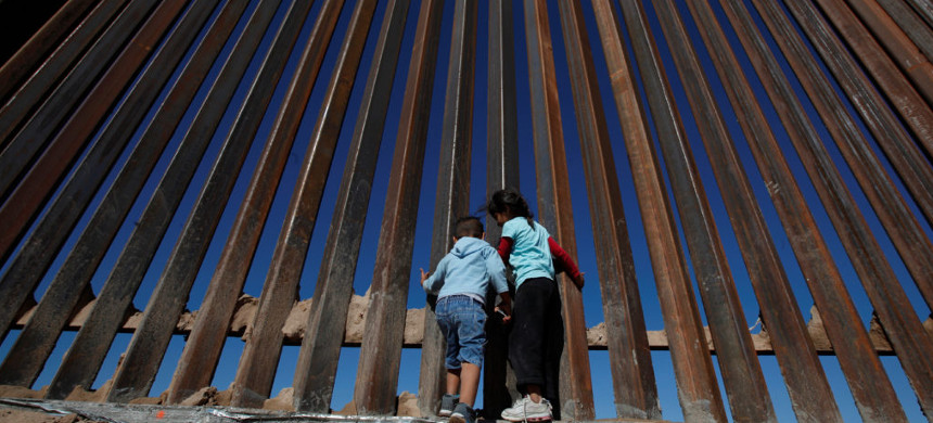 Children play at a newly built section of the U.S.-Mexico border wall. (photo: Getty)