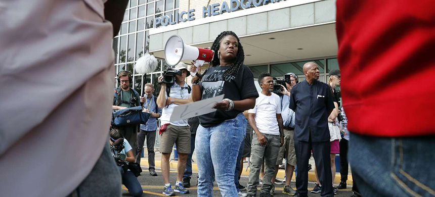 In this Sept. 17, 2017 file photo, Cori Bush speaks on a bullhorn to protesters outside the St. Louis Police Department headquarters. Bush said her car has been run off the road, her home has been vandalized, and in 2014 someone shot a bullet into her car, narrowly missing her daughter, who was 13 at the time. (photo: Jeff Roberson/AP)