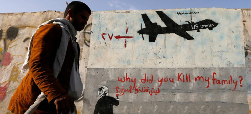 A man walks past a graffiti, denouncing strikes by U.S. drones in Yemen, painted on a wall in Sanaa, Yemen on November 13, 2014. (photo: Khaled Abdullah/Reuters)