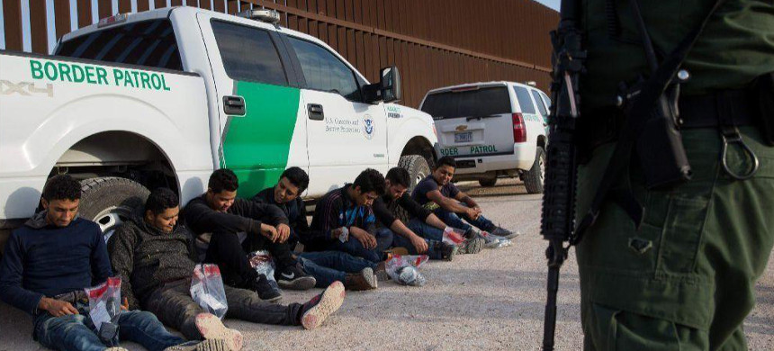 After being apprehended by Border Patrol, unauthorized immigrants wait to be transported to a central processing center shortly after they crossed the border from Mexico into the United States on March 26, 2018, in the Rio Grande Valley Sector near McAllen, Texas. (photo: Getty)