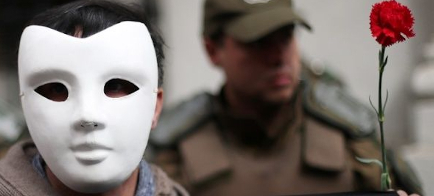 A man wears a mask in honor of former Chilean president Salvador Allende and the disappeared persons of the Pinochet dictatorship. (photo: EFE)