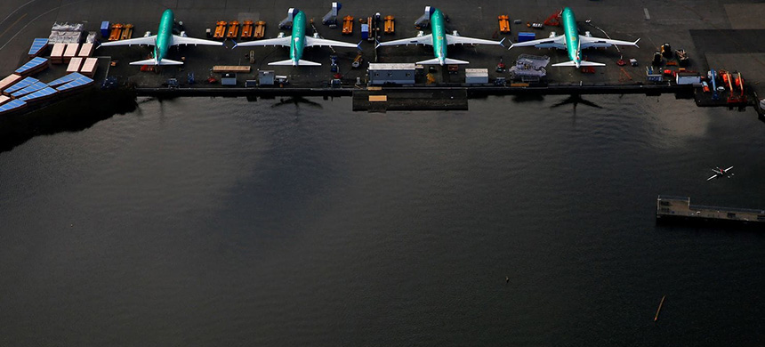 Rowers on Lake Washington near a line of 737 Max aircraft at the Boeing factory in Renton, Washington. (photo: Lindsey Wasson/Reuters)