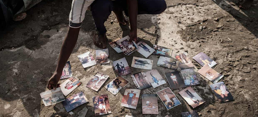 Joaquin Joao Chidja, 16, dries his family photos on the roof of a commercial building in Buzi, Mozambique, where the death toll from the cyclone has now reached 446. (photo: Yasuyoshi Chiba/AFP/Getty Images)