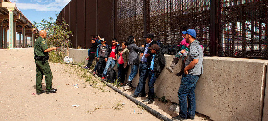 A group of 22 migrants from Honduras, Guatemala and Salvador await processing underneath the Paso Del Norte Bridge on March 28, 2019, in El Paso, Texas. (photo: Christ Chavez/Getty)