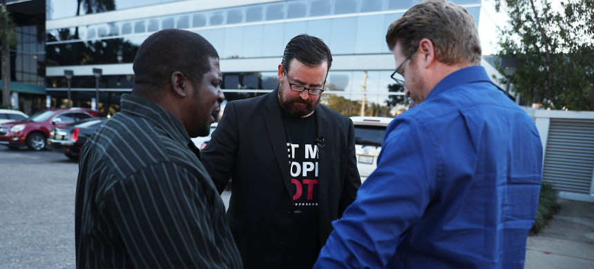 Permon Thomas (l) prays with Neil Volz (c) and Lance Wissinger (r) before Volz and Wissinger register to vote on January 8, 2019, in Fort Myers, Florida. (photo: Getty)