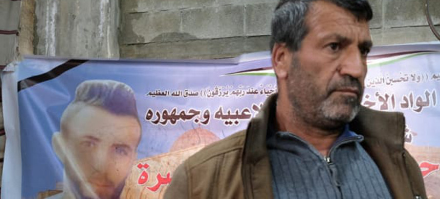 Jamal, Ahmad Manasra's father. A mourning poster for Ahmad is in the background. (photo: Alex Levac/Haaretz)