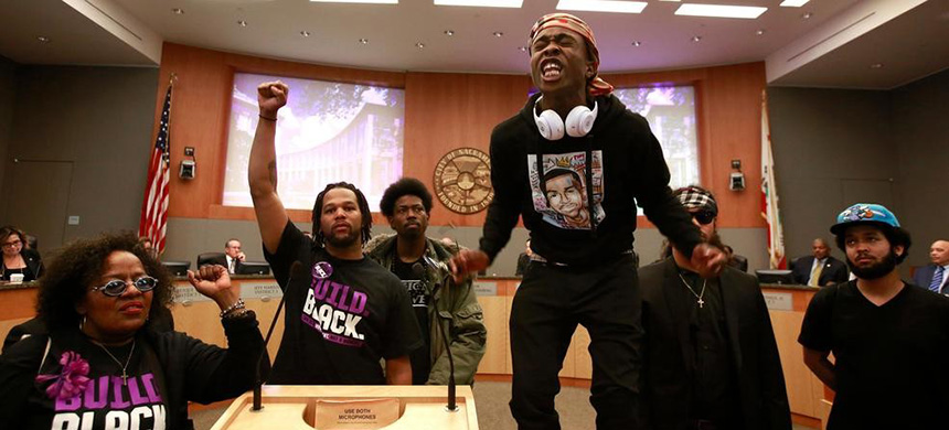 Stevante Clark stands on a desk as he shouts the name of his brother Stephon Clark, who was fatally shot by police a week earlier, during a meeting of the Sacramento City Council in Sacramento, California. (photo: Rich Pedroncelli)