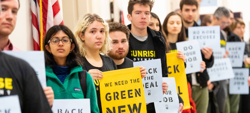 Members of the Sunrise Movement hold up signs calling for a Green New Deal. (photo: Getty)