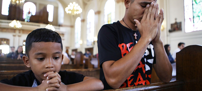 Honduran father Juan and his six-year-old son Anthony worship during Sunday Mass in Oakland, California. (photo: Mario Tama/Getty Images)