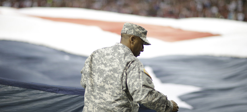 Paid advertisement? A soldier holds an American flag before the first half of a 2013 NFL football game between the Atlanta Falcons and the New England Patriots in Atlanta. (photo: David Goldman/AP)