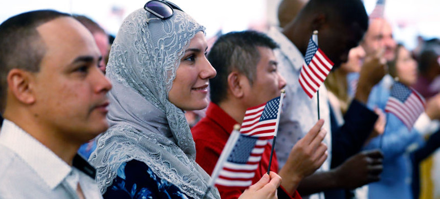Newly-naturalized citizens hold up small American flags after taking the Oath of Allegiance. (photo: Wilfredi Lee/AP)