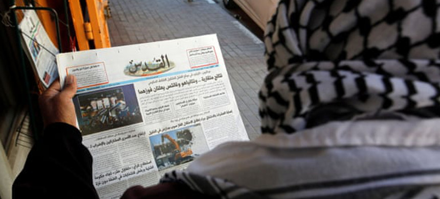 Palestinian man reads a local newspaper with news of the Israeli election, in Hebron, in the Israeli-occupied West Bank. (photo: Mussa Issa Qawasma/Reuters)